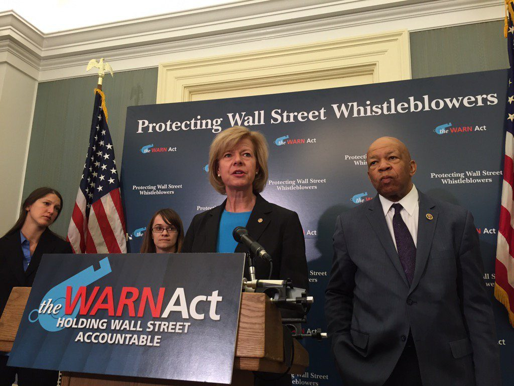 Sen. Tammy Baldwin speaks at a podium to introduce the WARN Act to enhance whistleblower protections.